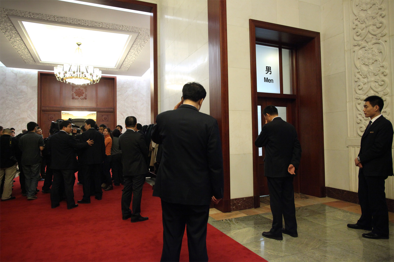 Security guards for Zhang Chunxian, Secretary of the Xinjiang Provincial Committee of the CPC, stand outside the men's restroom during the Xinjiang Provincial Delegation Open Day, March 8, 2011. Zhang, not pictured, had stepped inside the restroom and journalists had attempted to follow him in to ask questions.