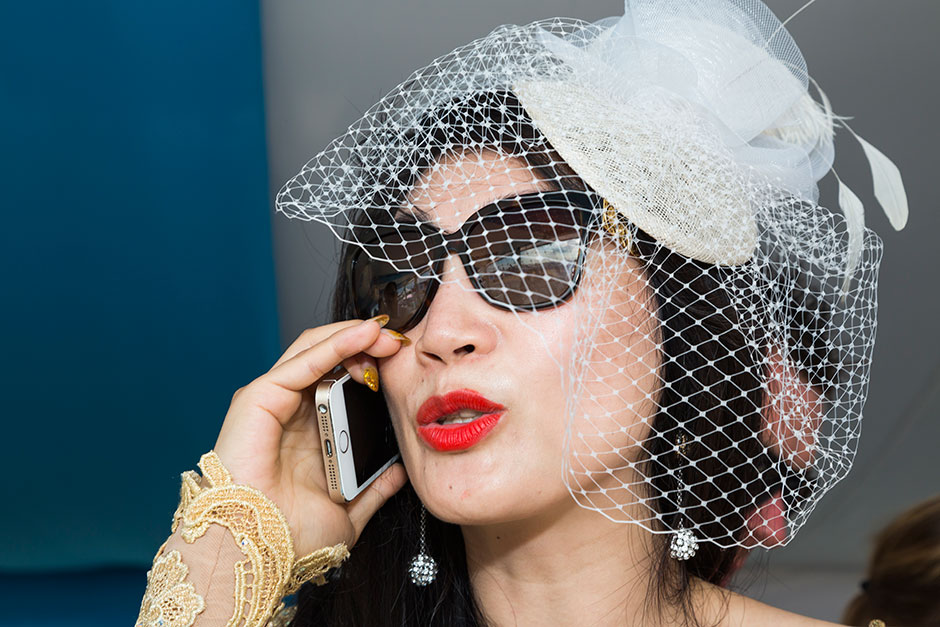 Siyu Yang talks on her gold-cased iPhone that matches both her gold dress and the Comte De Mazeray champagne infused with 24-karat gold flakes she hawked at the most exclusive yacht parties.