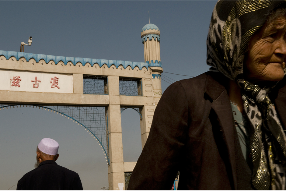 Uighurs walk beneath a video surveillance camera, which monitors street activity at a weekly marketplace in the city of Kuqa on September 12, 2008.