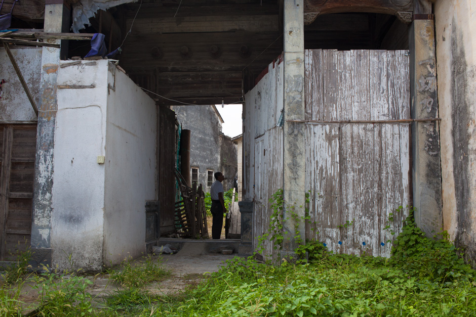Temporary walls and overgrown greenery partially mask the outer gates and stone pillars of the Mingxian Hall. A villager examines the entryway, which is rarely opened. Four wooden pegs above the gate indicate this hall was built to honor an ancestor who served as a fourth-rank civil official in the Qing court. A pair of stone drums and lions that used to flank the front gate are missing.