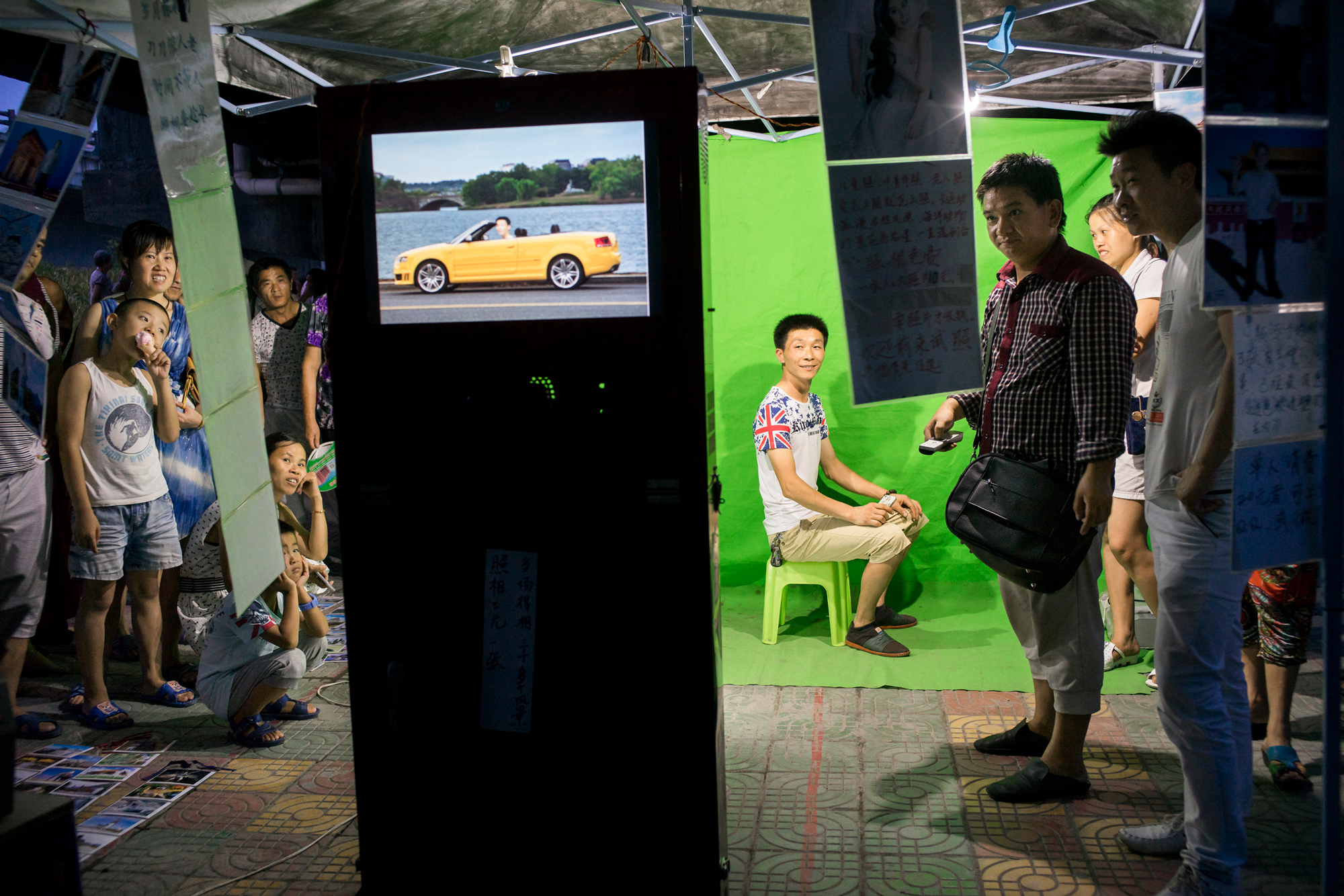 A man sits in front of a green screen at a photo booth where a digitally manipulated image with a simulated background is displayed on a screen, July 17, 2015.