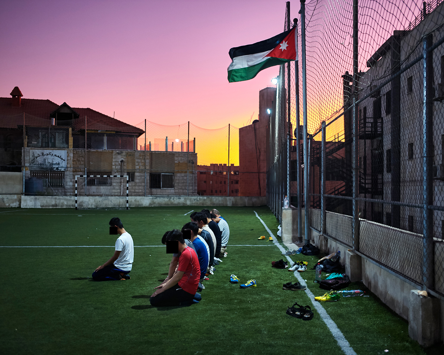 Umar and other Chinese Muslim students pray on a soccer field during a game, in Amman, September 2017.
