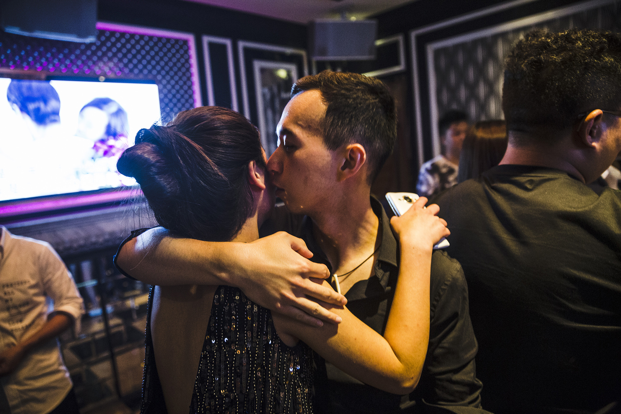 A student kisses a woman he met on the dating app Tantan, at a karaoke parlor, May 18, 2015. The students' final exam involves inviting at least two women they meet in the real world or on Tantan to a party at a karaoke parlor.