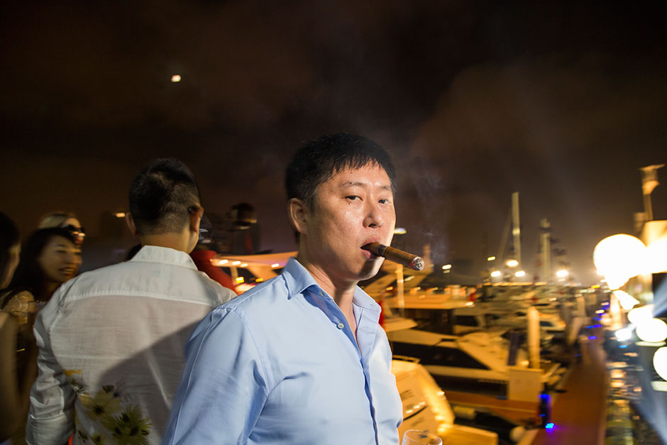 A vendor of high-end vintage cigars smokes some of his product at a private Sanlorenzo cocktail party in Dalian.