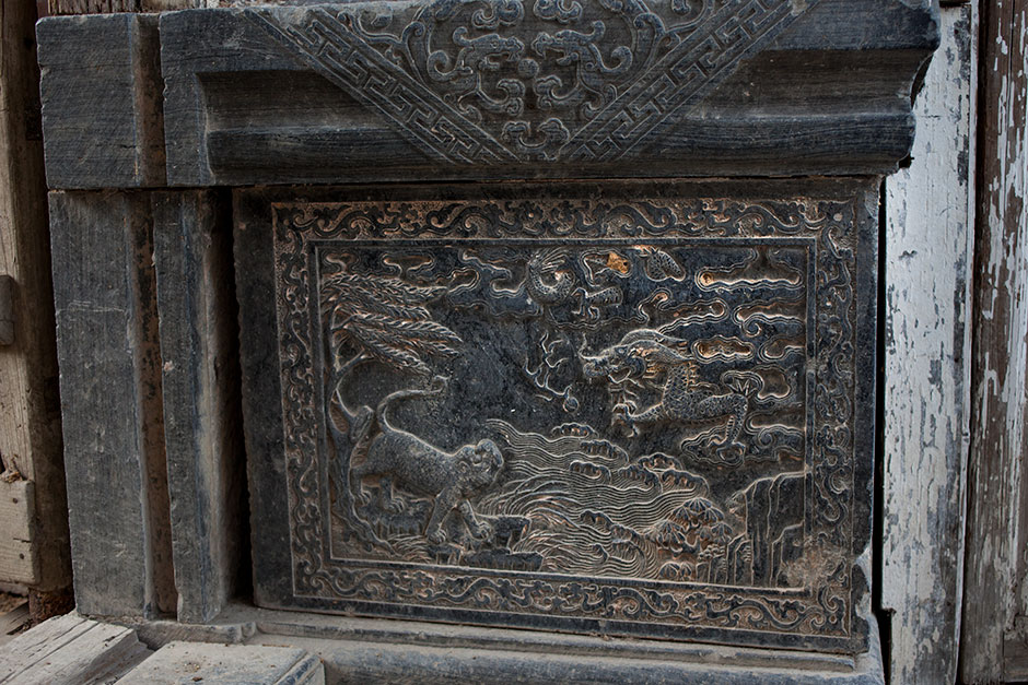 A stone carving of a tiger, on an elaborate stone plinth peeking out from behind a wooden barricade, is another sign the hall was built to honor a high-level official. As the tourism business grows in the region, stone carving has again become a lucrative business.