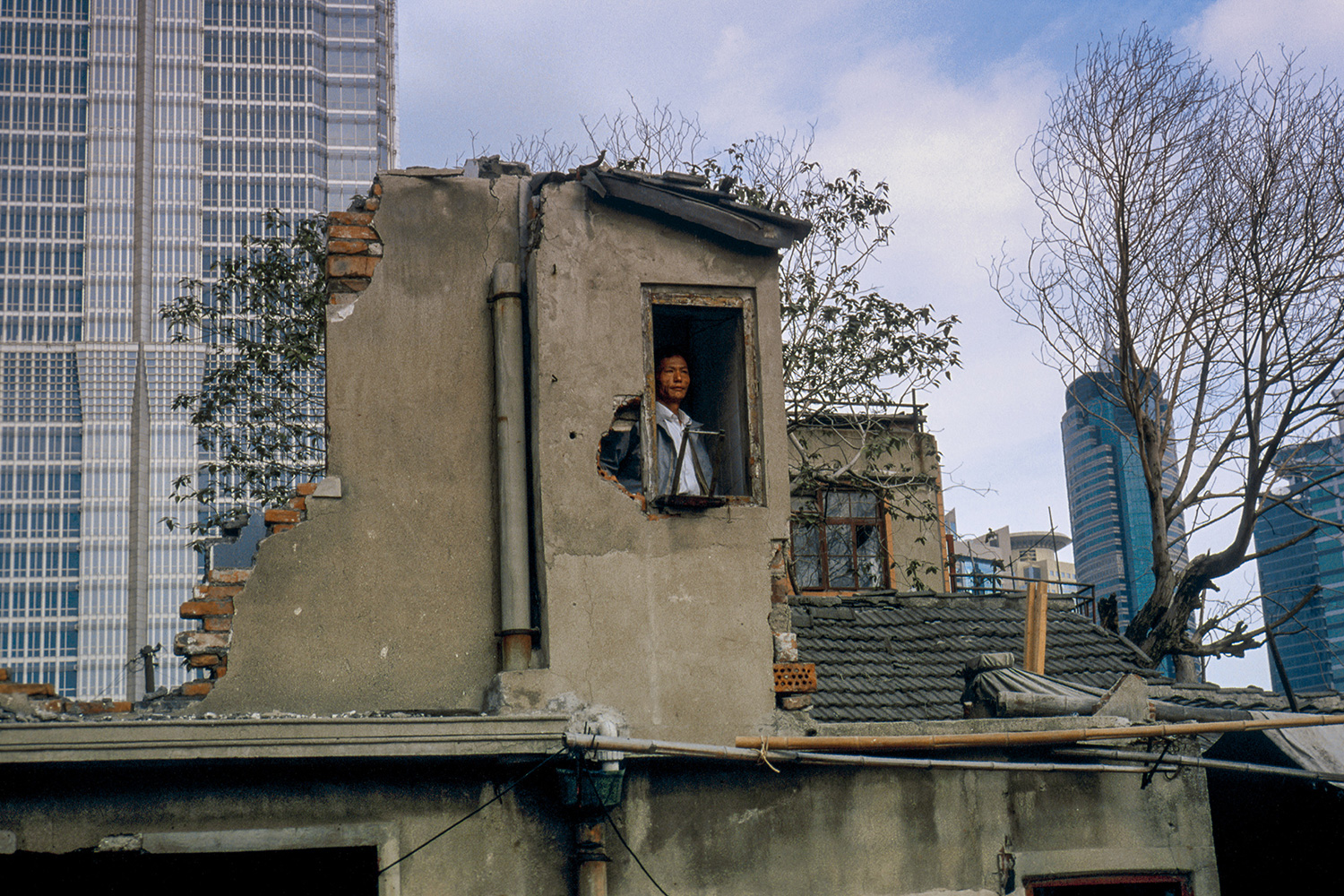 A resident refuses to leave his home at the base of the Jin Mao Tower, 1998.