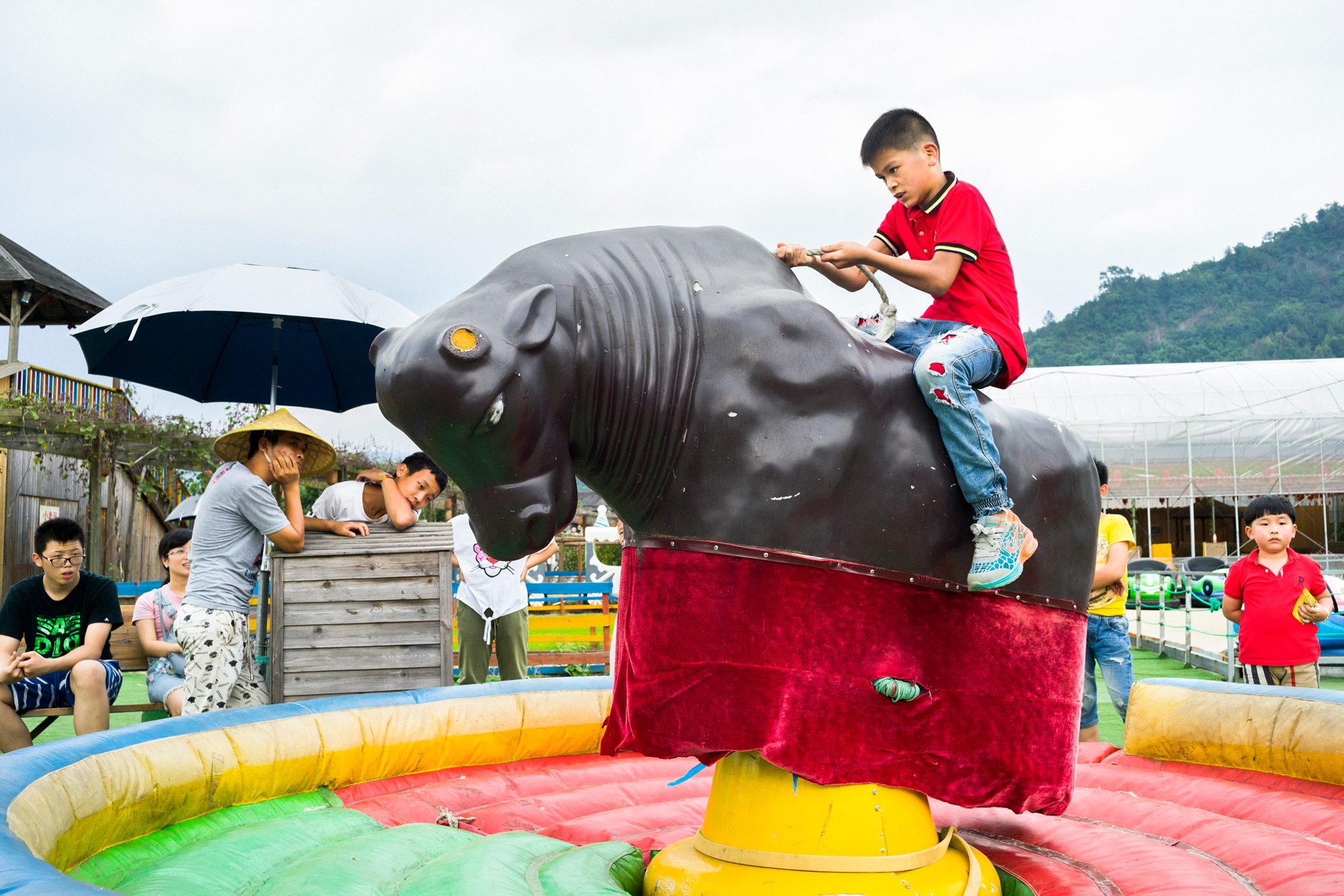 A child rides a mechanical bull at a leisure farm, a type of resort, in Huling township, October 3, 2016.