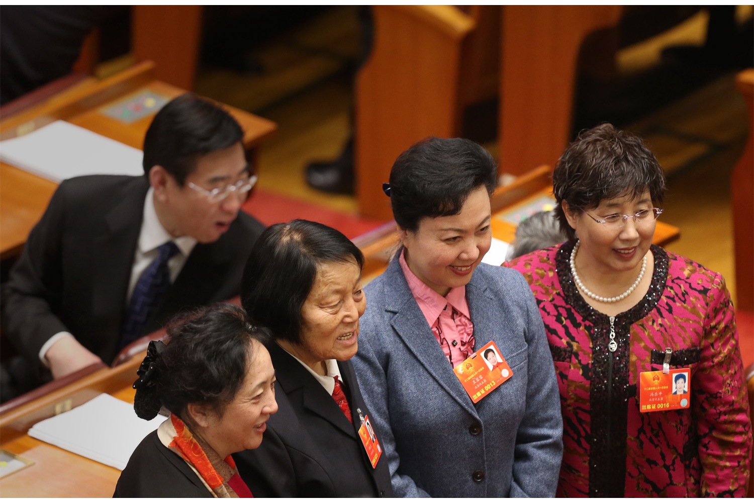 A deputy in ethnic clothing, bottom left, stands for a photo with other female deputies before the start of meetings, March 5, 2013, in the Great Hall of the People.