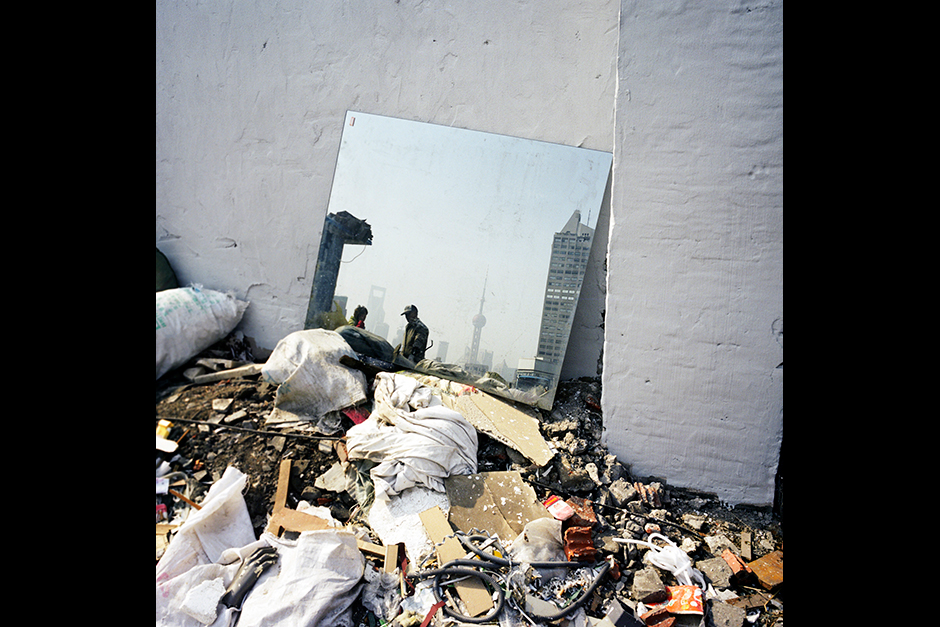 The skyline of Shanghai's Lujiazui Financial Center in Pudong District is reflected by a mirror lying in a demolition site, January 2010.