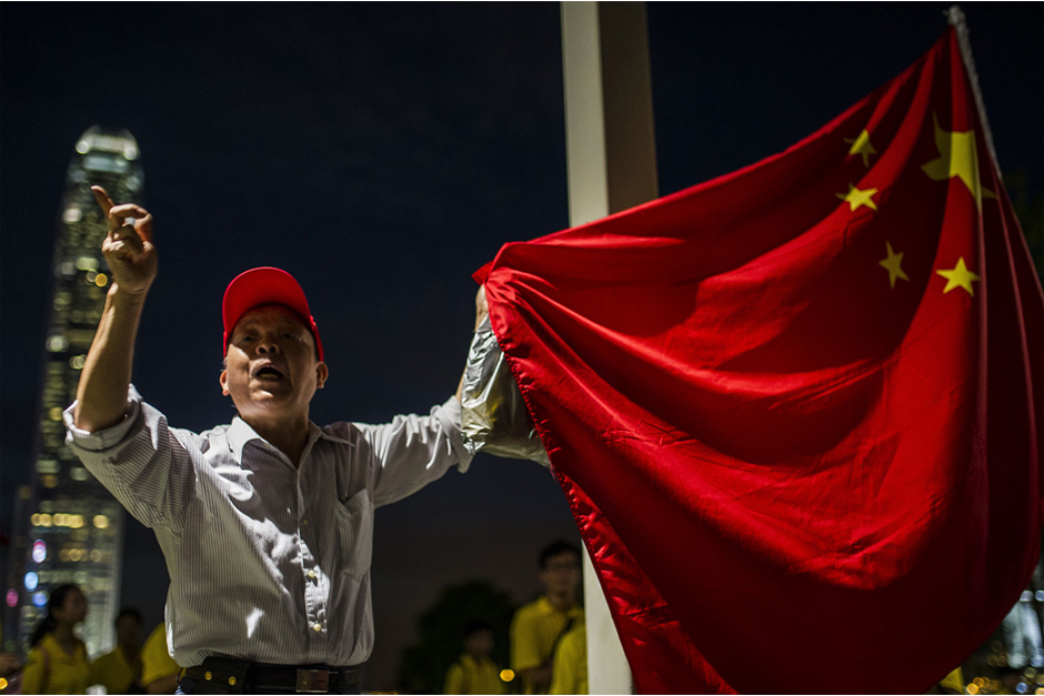 A pro-Beijing demonstrator holds a Chinese flag and shouts to pro-democracy activists in Tamar Park on September 26. (Photo by Xaume Olleros/AFP/Getty Images)