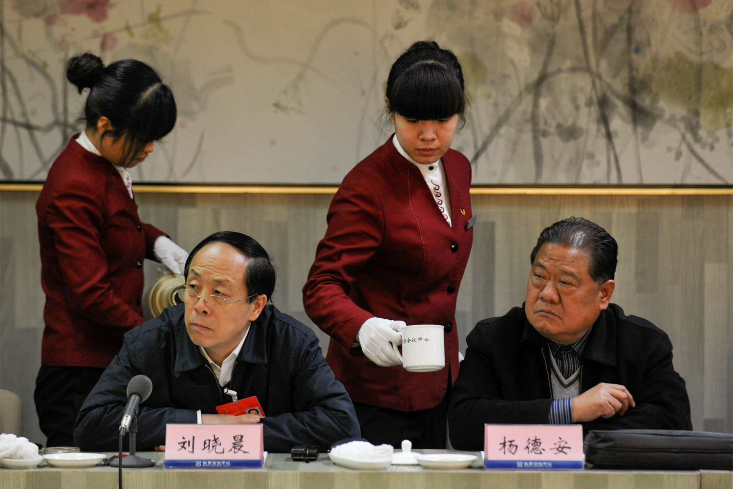 NPC deputies Liu Xiaochen (seated left) and Yang De'an listen to a speech by a Beijing deputy during a forum between NPC and Beijing Municipal People's Congress deputies, as two female waitresses pass to refill tea, January 20, 2011.
