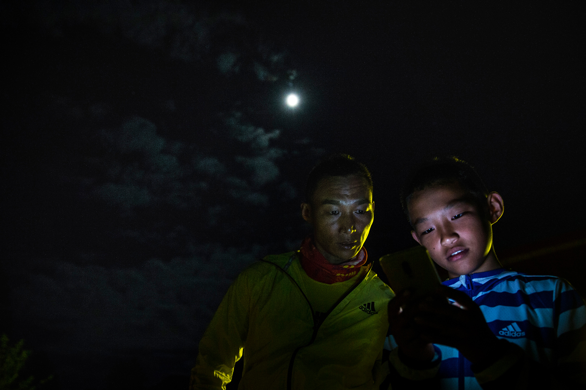 Runxi uses his dad's phone to try to find a hotel for the night, in Guxiang Village of Nyingchi city, Tibet, August 1.