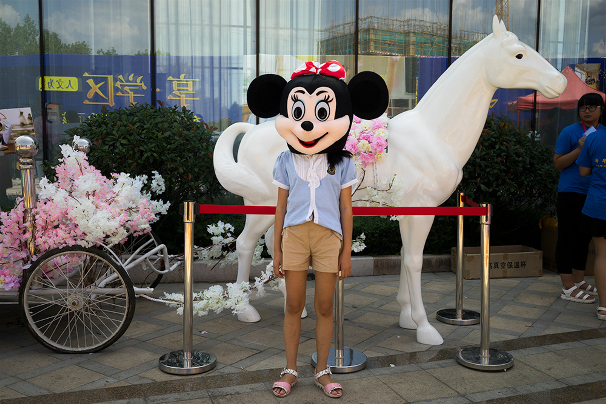 A child wears a Minnie Mouse costume for a photo in Mayu township, October 3, 2016. A real-estate sales center set out the cartoon objects and costumes to attract customers.