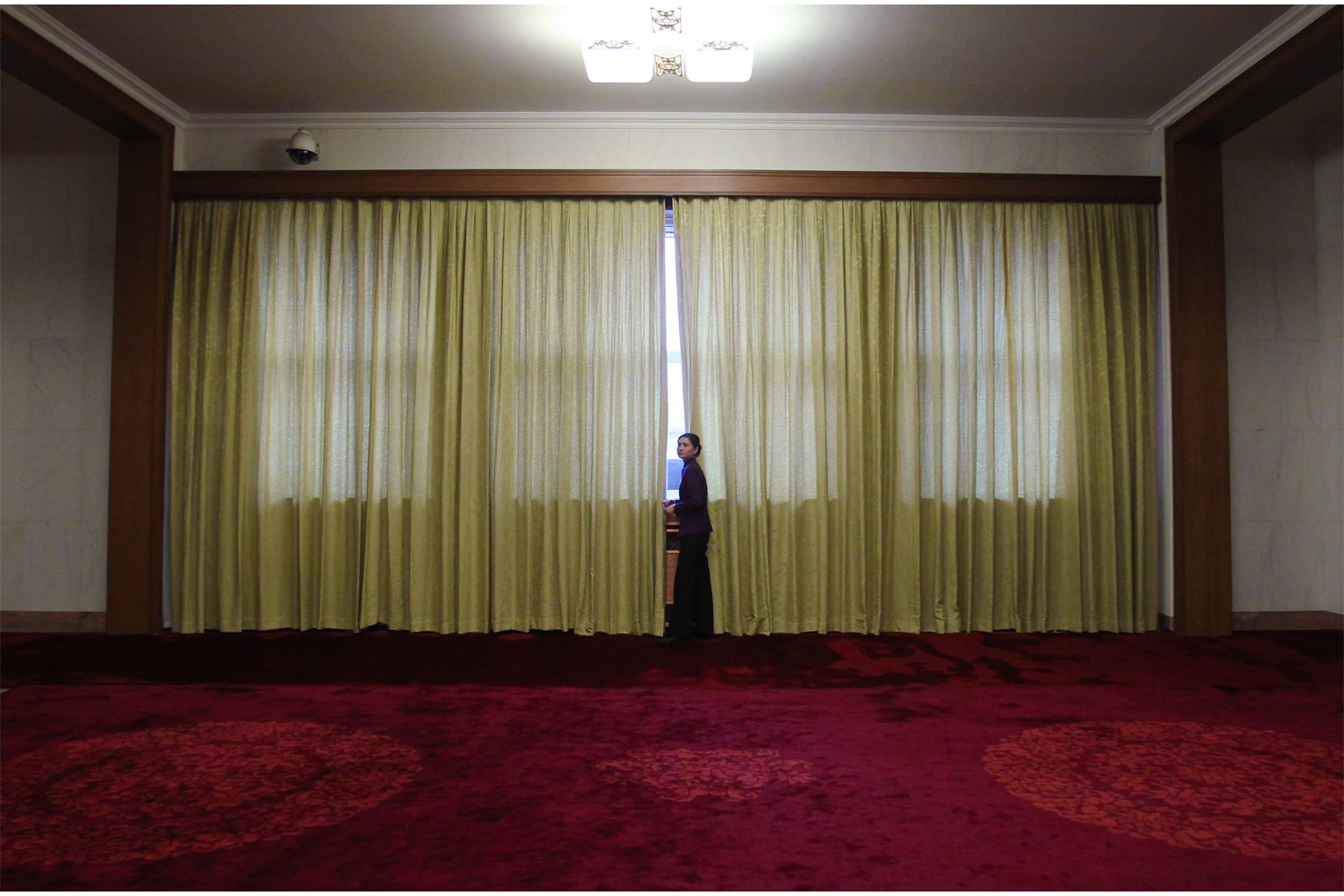 A waitress stands by a window in the corridor outside the Great Hall of the People, March 10, 2011, during the afternoon of the Fourth Session of the 11th CPPCC.