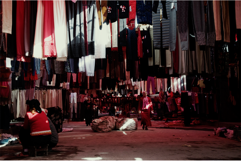 At a Kuqa weekly market, shawls, pants, and other cloths hang on sale in one of the many stalls.