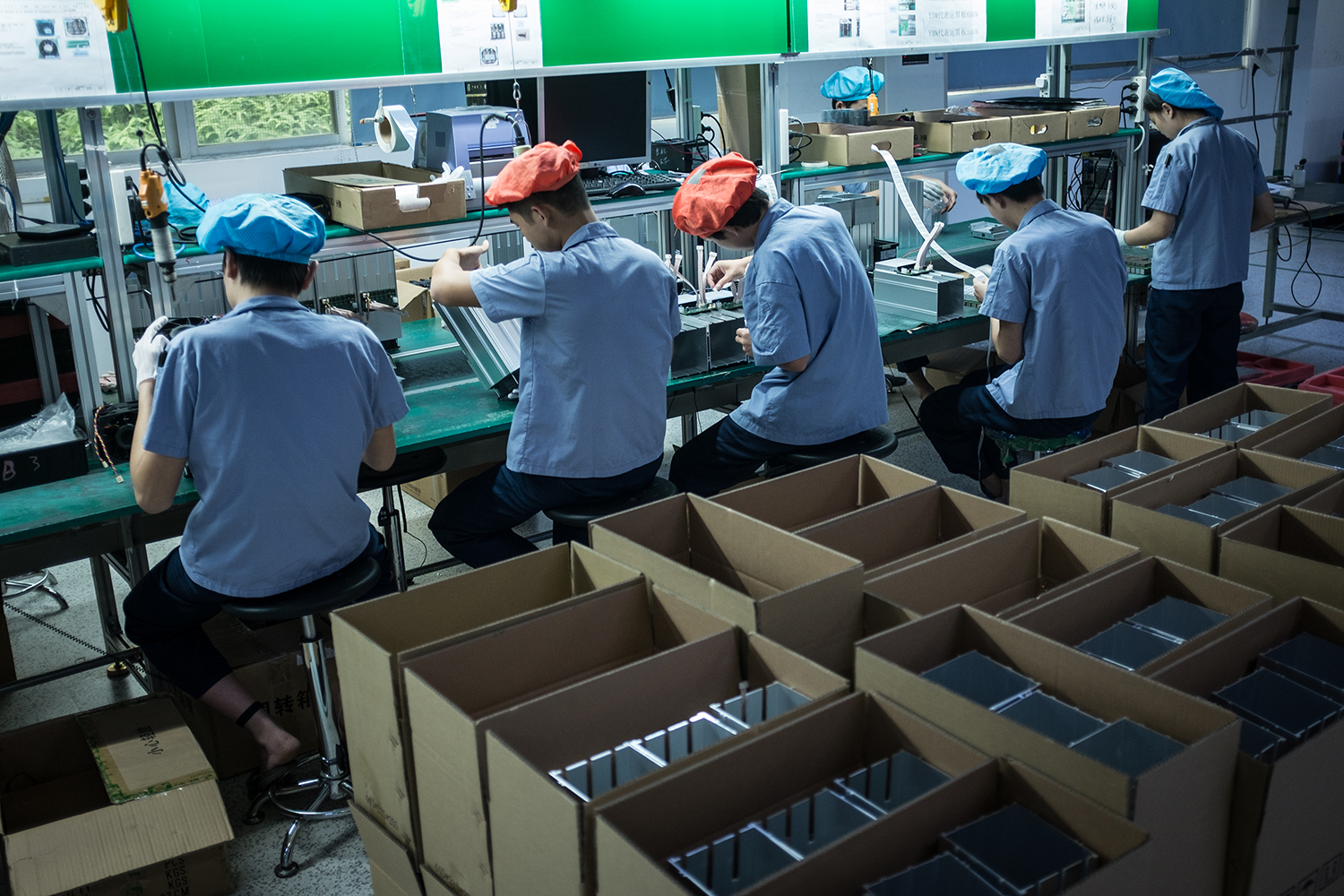Employees work on an assembly line of AntMiner S9 mining machine at Bitmain's manufacturing base, Shenzhen, November 9, 2016.