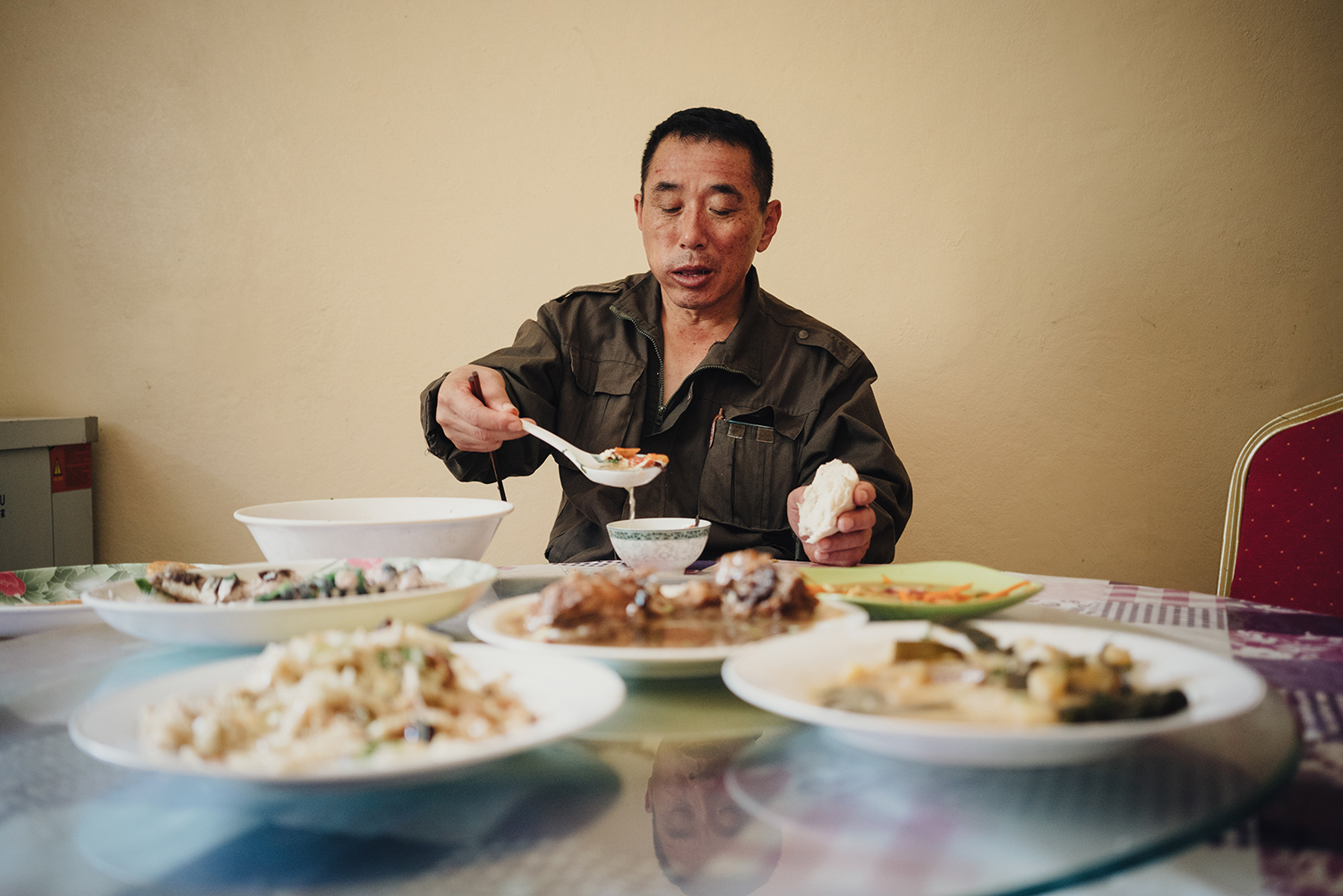 Liu Zhaoquan, 60, the supervisor at Lem Seafood, eats at the factory cafeteria, June 29, 2016. Liu comes from Shandong province. He formerly worked as a carpenter. In 2011, he came to Nouadhibou to help his nephew oversee the fishmeal factory. He goes back to China once every two years. The factory provides Chinese employees Shandong-style dishes, one of the few reminders of home, Liu says.