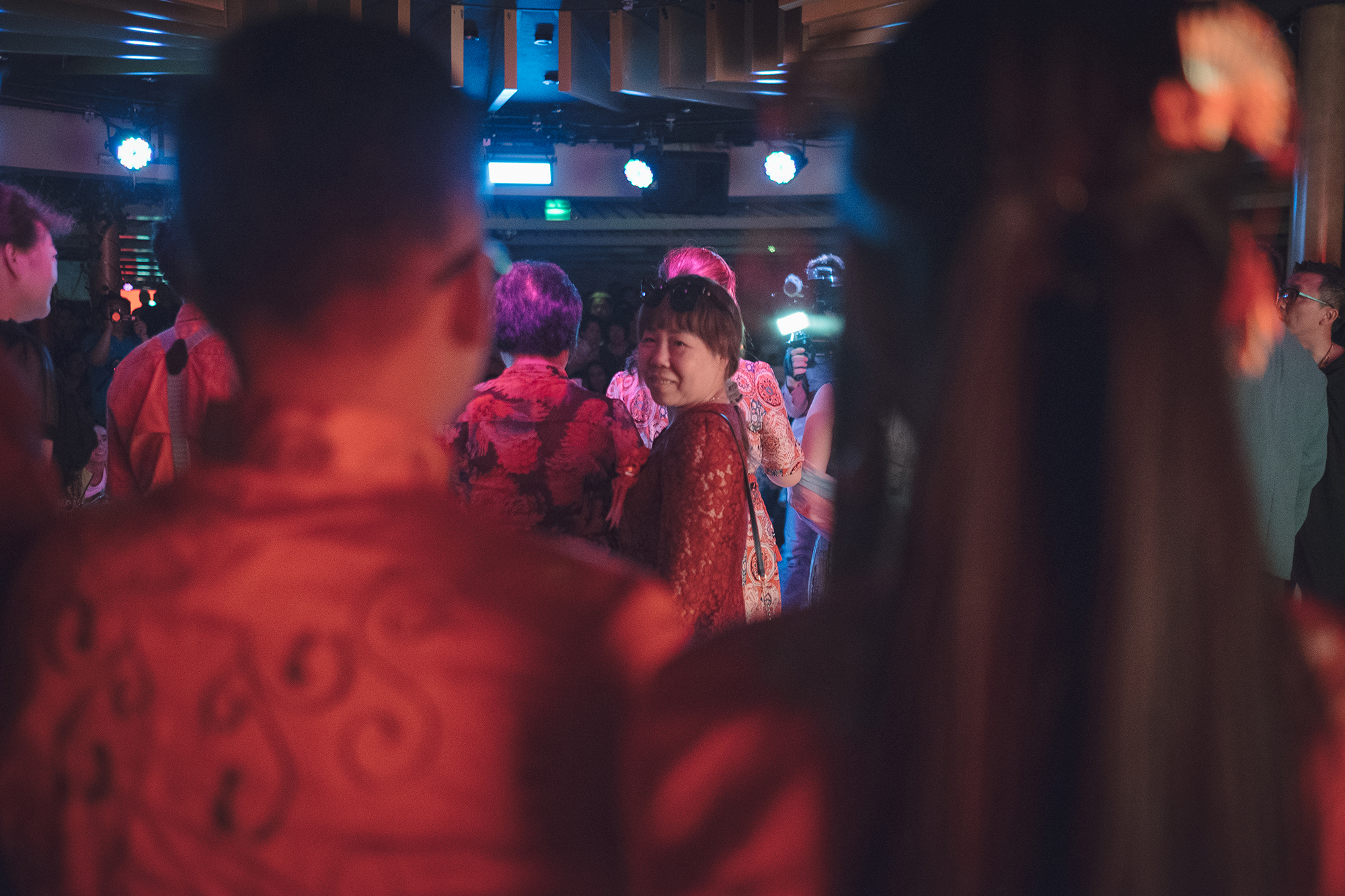 Hesitating at first, Mrs. Zheng finally decides to go up onstage with other parents to give blessings in front of the guests. She looks back at Chen and Yang.