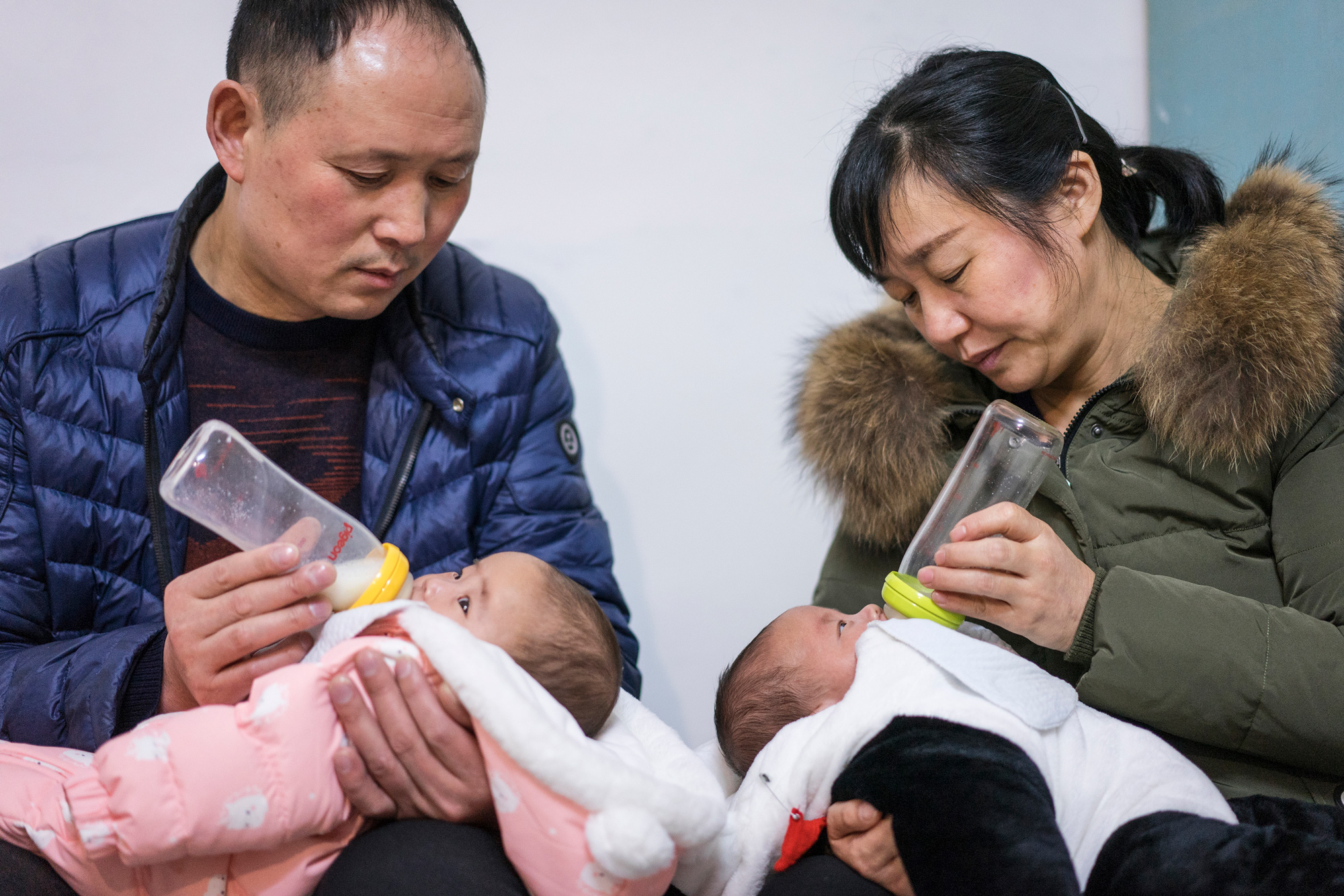 "Zhiying and Fangguo feed the twins at home, in Suizhou, March 2, 2018. ""The way to take care of babies is so different from when Ti was young. It's hard for us to keep up with the times,"" Fangguo says."