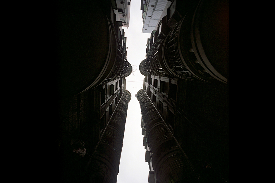 "Extremely narrow alleys between buildings are common in urban villages, such as in this scene in Gangxia West Village. Here the buildings on each side are referred to as ""handshake"" buildings. These narrow alleys are fire safety concerns and are not in compliance with building code. But housing is more complex than building codes and blueprints."