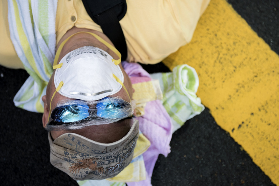 A man wearing a facemask and plastic wrap on his sunglasses sleeps at a pro-democracy protest on Nathan Road. (Photo by Alex Ogle/AFP/Getty Images)