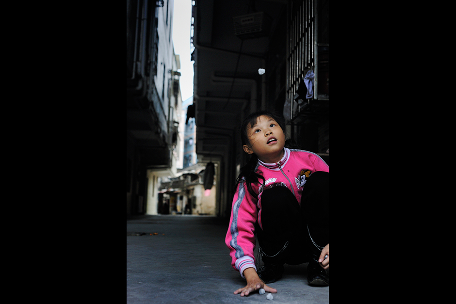 In Wuwucun, children's parents do not have much extra money to spend on toys.  Here a girl uses bits of dried cement to play jacks in the entryway of the multistory apartments next to the village.