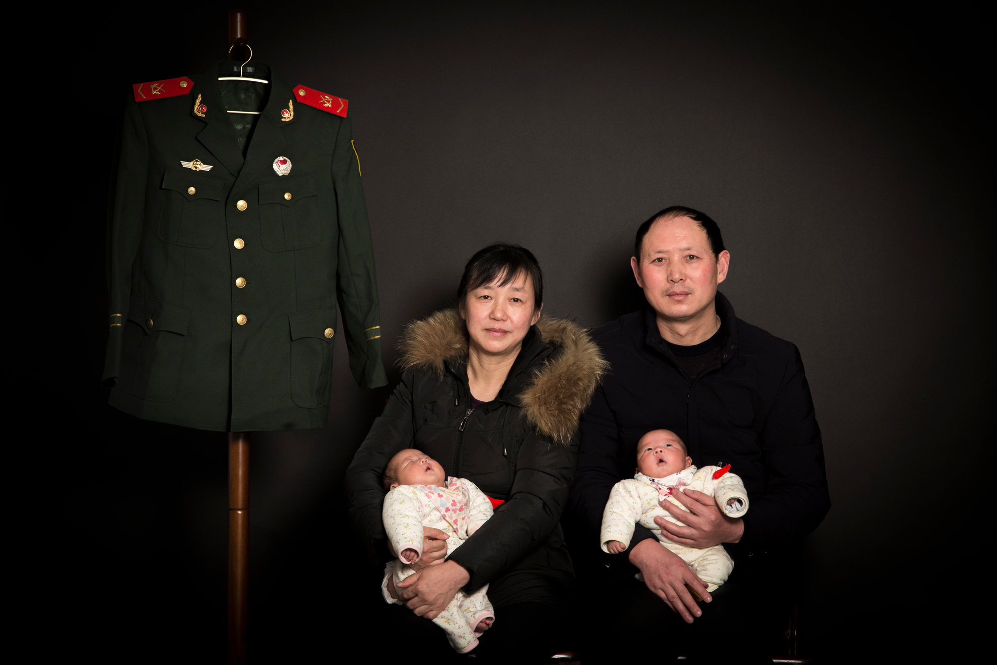 Zhiying and Fangguo hold the twin babies to pose for a family photo with Ti's military uniform, at their home in Suizhou, February 10, 2018.