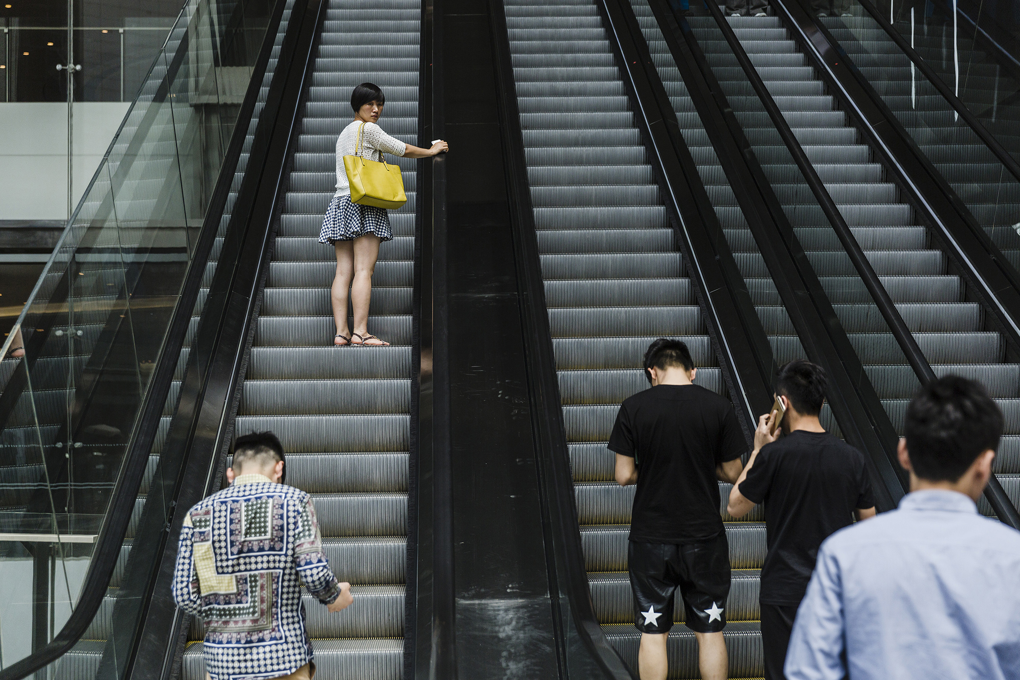A woman glances at Puamap's students on an escalator in a shopping mall, May 15, 2015.
