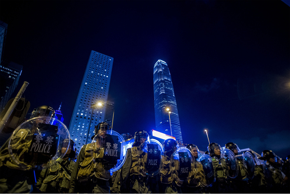 Police officers stand in front of pro-democracy protesters. (Photo by Xaume Olleros/AFP/Getty Images)
