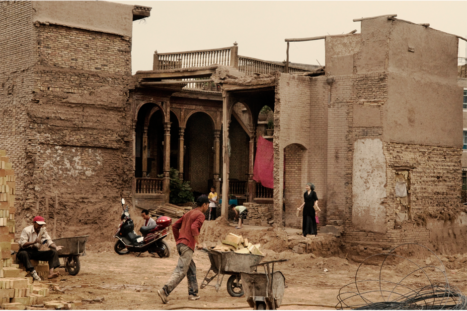 Next to a construction site in the old city of Kashgar, inhabitants of a traditional courtyard house stand by the wall of their house, demolished a few hours earlier, in June 2009. The residents were left to clean up the rubble. The city, one of the oldest on the Silk Road, has been demolished and rebuilt, with many of its inhabitants forced to move to the outskirts.