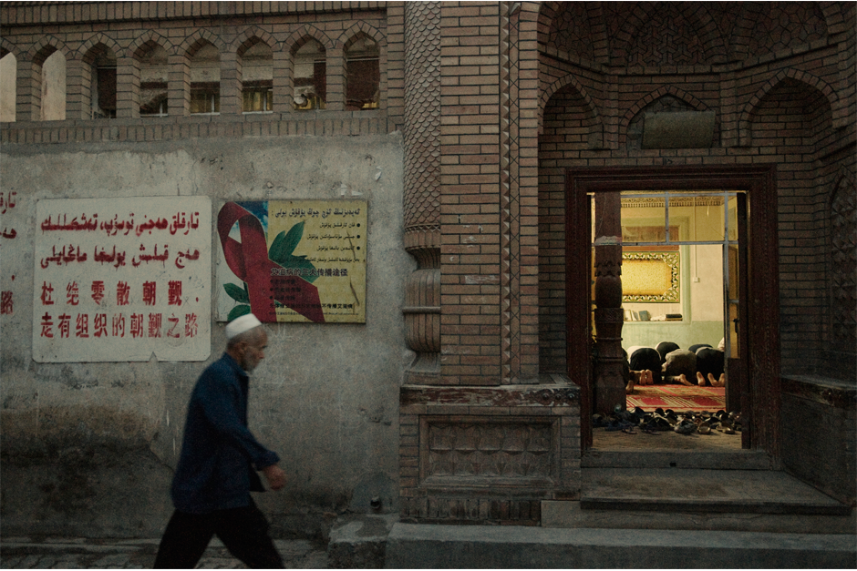 "A resident of Kashgar's old city heads to a local mosque for evening prayer in the summer of 2009. On the wall of the mosque next to a board promoting AIDS awareness is a legal reminder in both Uighur and Mandarin: ""Individual pilgrimage is strictly prohibited. Take the path of organized pilgrimage."" The pilgrimage to Mecca, one of the pillars of Islam, is strictly controlled by the government. In general, it is much more difficult for Uighurs than for Han Chinese to obtain a passport and travel overseas."