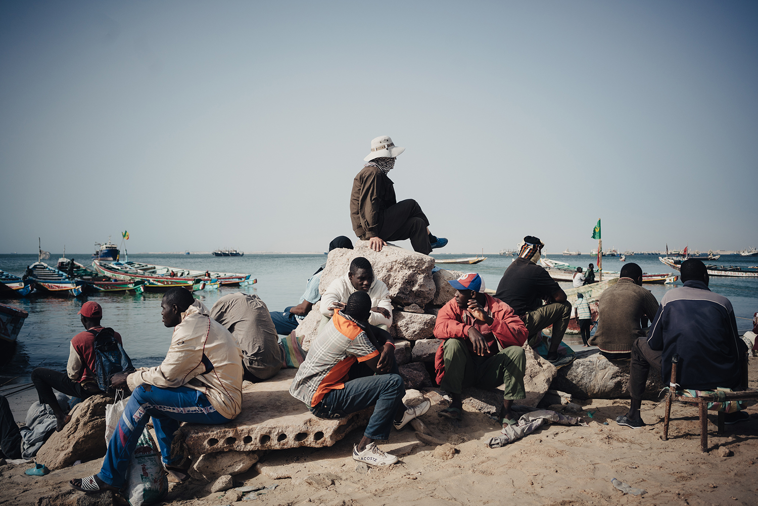 In the morning, Liu, in a white hat, oversees the transfer of fish from boats to trucks on the shore, June 29, 2016. On average, the factory goes through 200 tons of fresh fish per day, mainly supplied by Senegalese and Mauritanian boats. But, as the number of fishmeal factories has increased, demand often exceeds supply and some Chinese factories have started to form their own fishing fleets.
