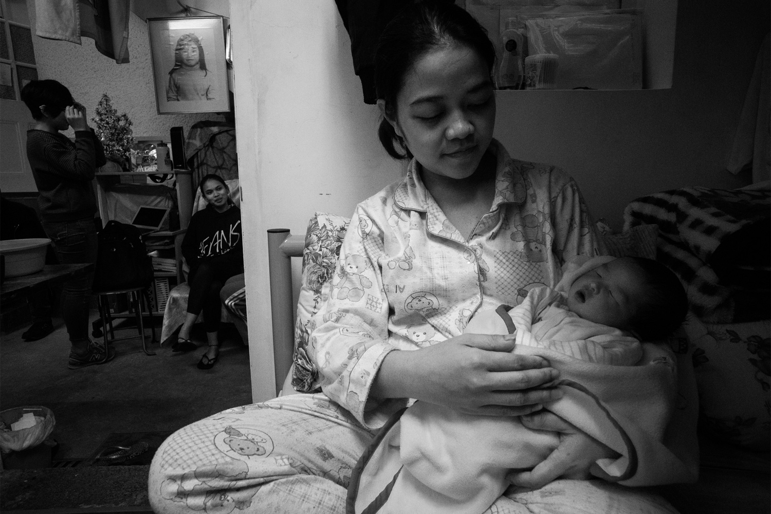 Queenie, a Filipina domestic worker, holds her seven-day-old baby, Yuan. When Queenie learned that she was pregnant, she asked her employer to allow her to return to the Philippines. The next day, the police arrived at her workplace and told her that her employer had accused her of stealing an earring. She was ultimately convicted of that crime and sentenced to imprisonment. Queenie believes her employer wanted to avoid paying her maternity leave. Prison authorities brought her to a hospital to deliver her baby, who was born on January 1, 2015, and since she had served out her sentence she was released from custody a few days later. With nowhere to go, Queenie ended up at the Kowloon Union church, where a minister saw her crying. She was referred to Bethune House for shelter and aid.
