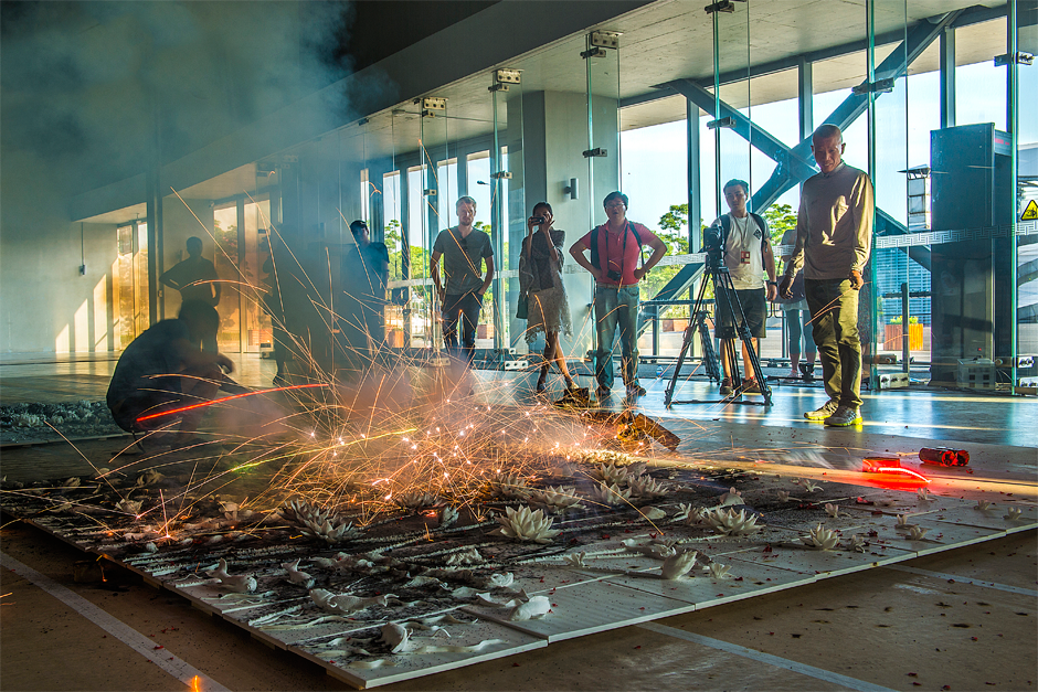 "Cai Guo-Qiang, right, ignites firecrackers on ""Summer,"" a gunpowder drawing on porcelain, as part of the installation ""Spring, Summer, Fall, Winter"" in the Great Hall of the Power Station of Art, 2014. (Photo by Lin Yi, courtesy Cai Studio)"