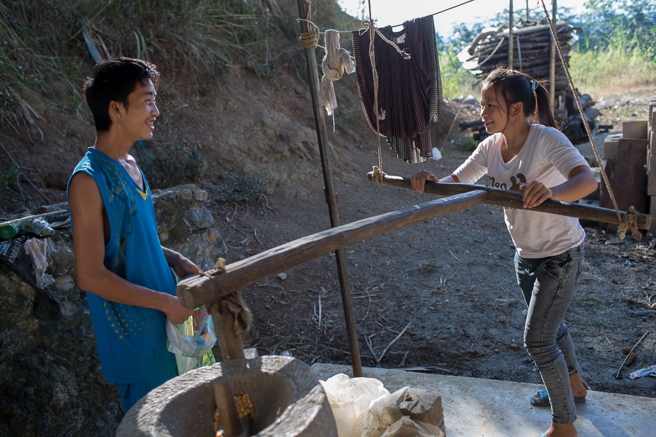 Ming and Cai use a neighbor's hand mill to grind corn. Courtship is brief and much of the relationship building happens when the young couples are already married.