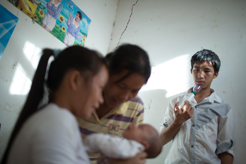 "Ming holds a breast pump as he watches his wife, Cai, and his mother care for his newborn at home. ""My single friends stopped calling me after I got married, and my life got boring,"" Ming said."