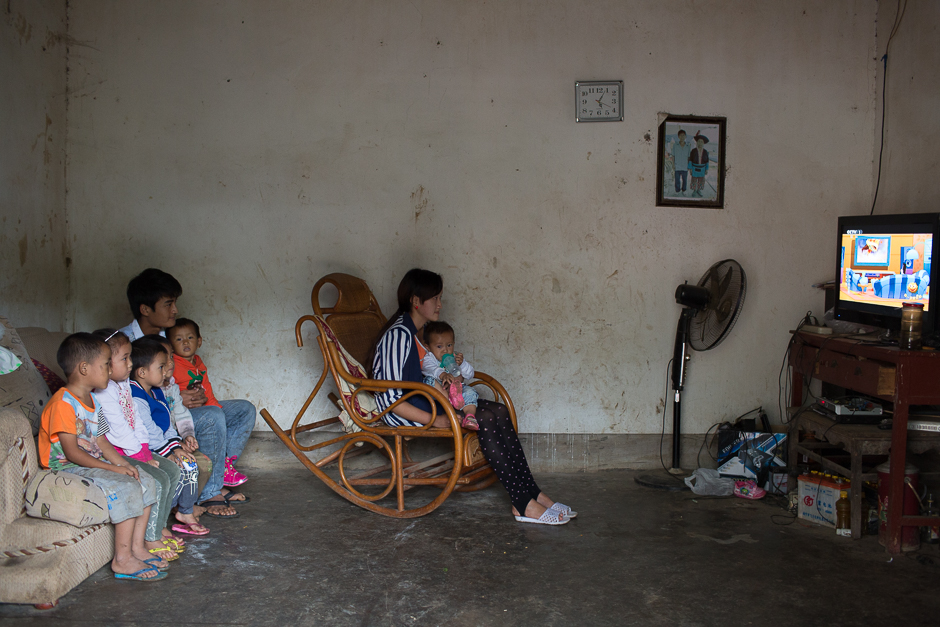 "Xin, 16, holds her one-year-old daughter on her lap as she sits in a rocker watching a popular Chinese cartoon, ""Big Head Son and Small Head Father,"" at her home in Guangdong village, Mengla county. Xin and her husband, seated with neighborhood children on the sofa, started dating three years ago when they were in fifth grade. They dropped out of school when they got married more than a year ago."