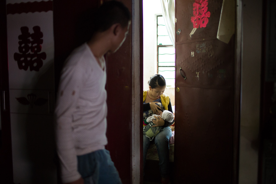 Fang, 18, looks in on his wife, Li, 16, as she nurses their one-month-old baby at home, in Guangdong village, Mengla county.