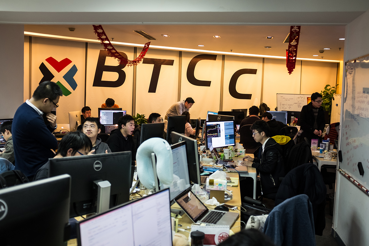 "Employees work at BTCChina (BTCC)'s office, in Shanghai's financial district, January 13, 2017. BTCC was founded in 2011, and is now one of China's largest Bitcoin exchange platforms. According to its CEO Bobby Lee, Chinese people like the ""online gambling"" feel of Bitcoin's instability; also, with the Chinese government's restrictions on many investment channels, people welcome new ways to invest their money."