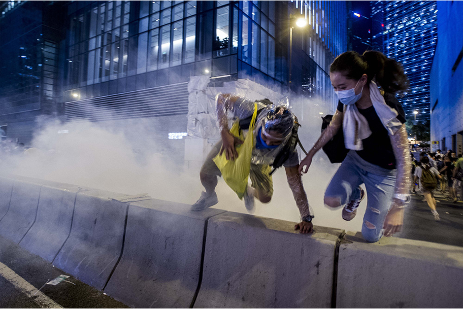 Pro-democracy demonstrators jump a barrier to escape a cloud of tear gas. (Photo by Xaume Olleros /AFP/Getty Images)
