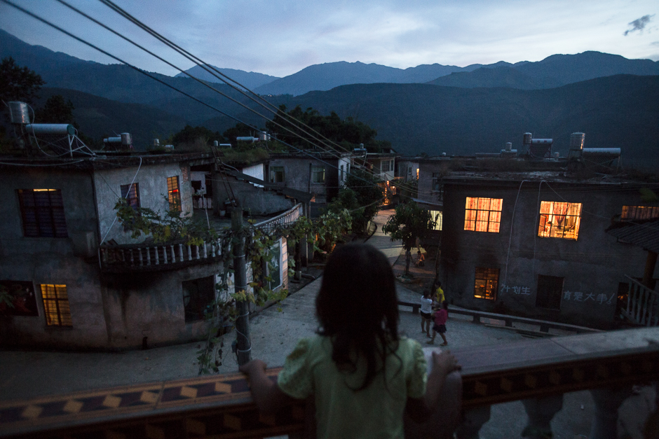 Seven-year-old Yuan looks out over her village from the balcony of a neighbor's home in Yangxi village, Zhemi county. Yuan has never gone to school because her mother never enrolled her. She said she doesn't know if she ever will go, and says she doesn't know if she wants to.