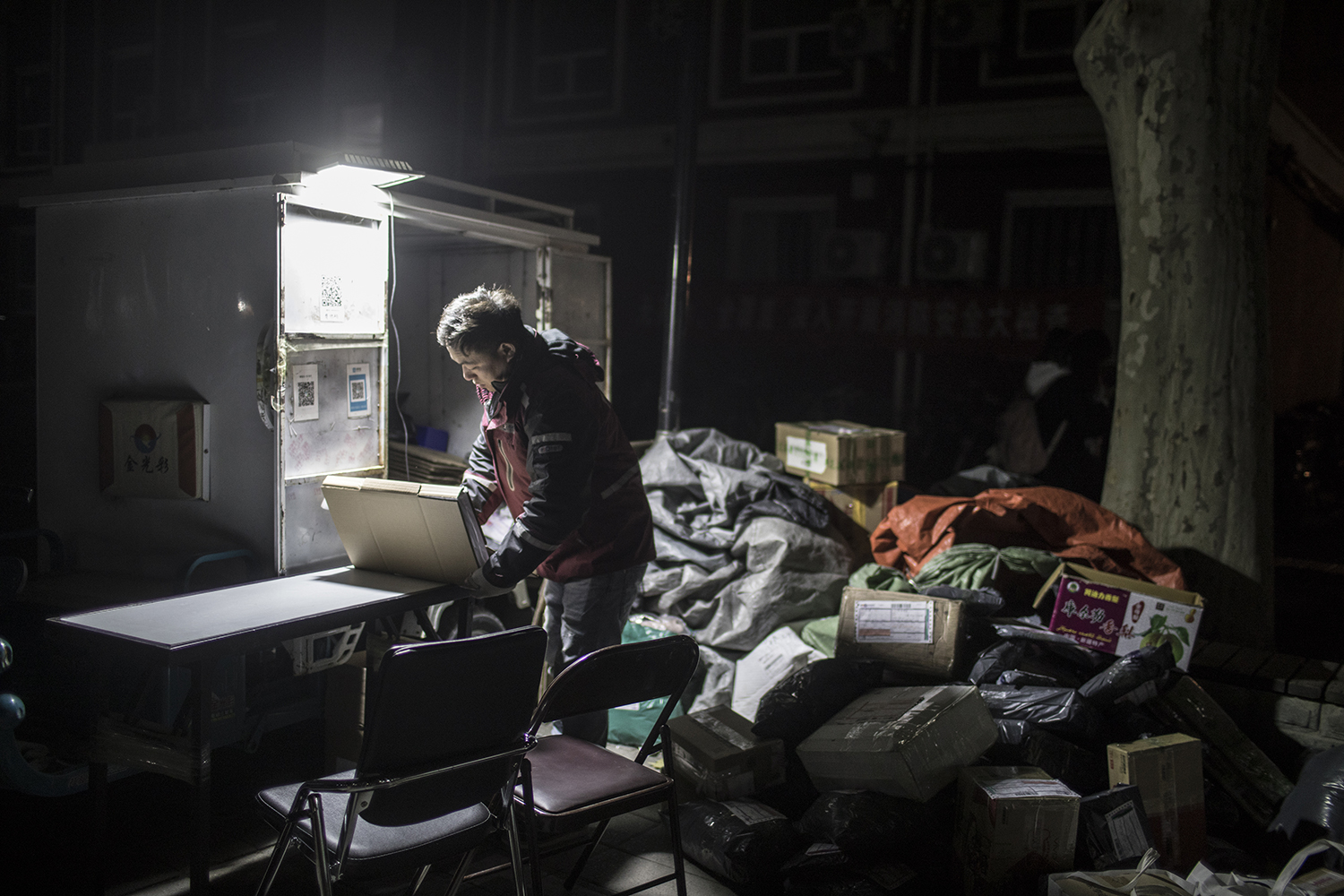 "November 31, 31-year-old delivery man Pan Yabei sorts packages at Beijing Youth Politics College. Pan's workload is heavy after Alibaba's Singles' Day sale. He has been working at the school for nine years but says he will have to leave Beijing soon because the home he rents is considered ""unsafe"" and he has been urged by authorities to move out. He says he can't find another affordable place to stay. (Feng Haiyong/Tencent Guyu Project)"