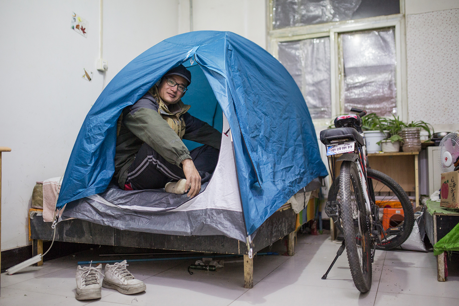 November 18, 30-year-old Xu Qinsheng stays in a tent on his bed to keep warm, in Banbi village, Beijing. He has lived here for four years. But the building hasn't installed heating yet because of new prohibitions on the burning of coal. As China tries to tackle air pollution by using cleaner fuel, shortages of natural gas leave some places without heat amid freezing winter temperatures. (Zhou Na)