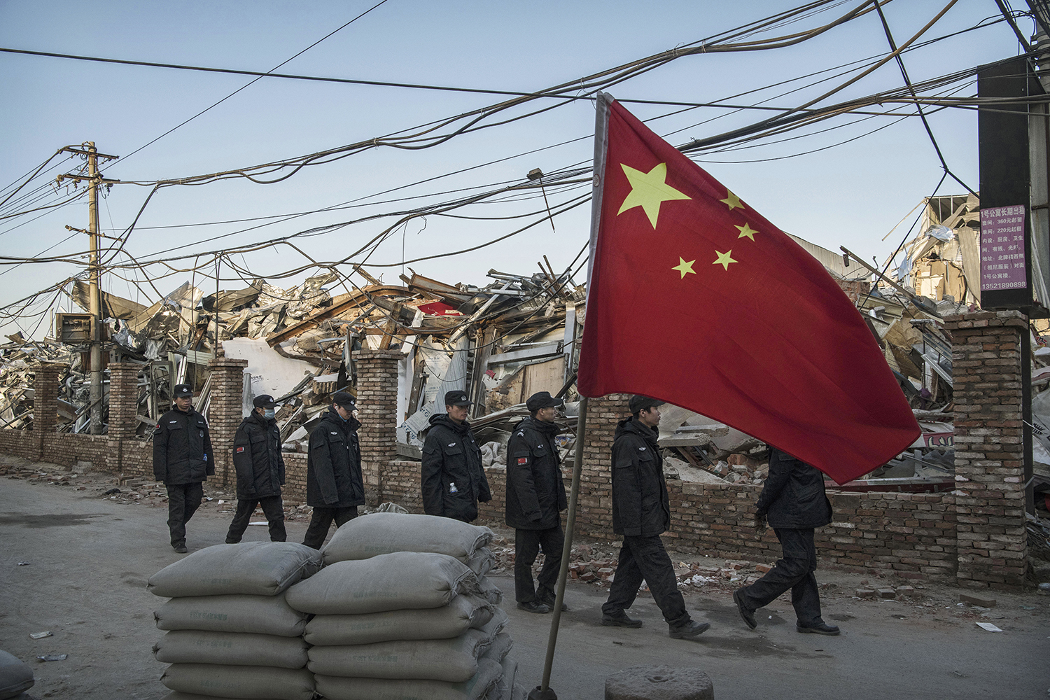 December 6, Chinese police walk in a line past houses and factories demolished by authorities in the Daxing District of Beijing. In recent weeks, thousands of migrant workers have been forcibly evicted in a sweeping government safety campaign following a deadly fire at a housing settlement. (Kevin Frayer/Getty Images)