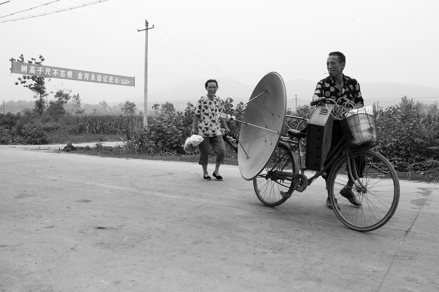 A farmer brings his dismantled TV antenna equipment with him as he leaves Jinhe. Nearly all material goods, with even the slightest bit of worth, were carted away; little was left behind.