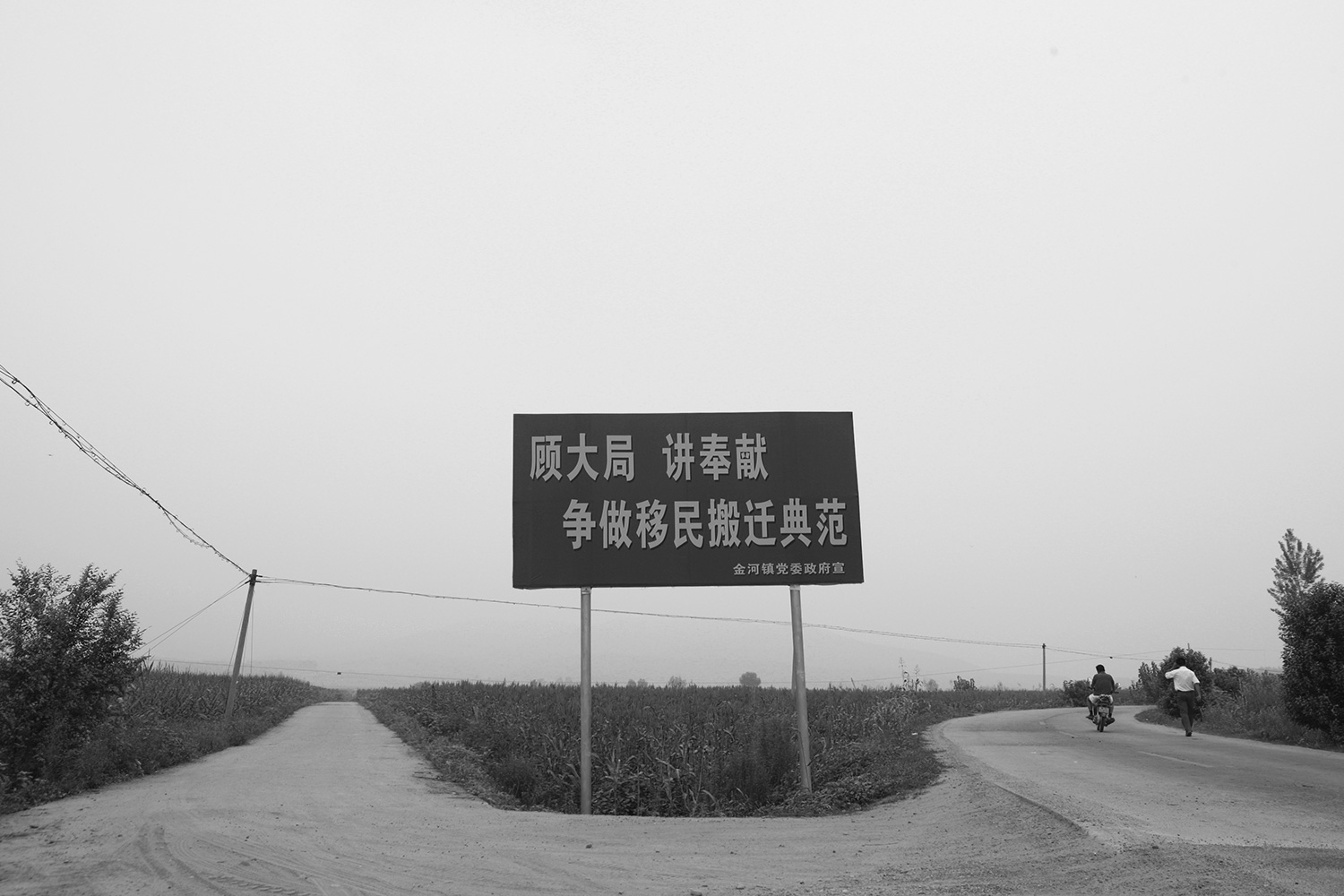 "Slogans like this one, which reads ""Look at the Big Picture, Be Willing to Sacrifice, Strive to Become an Exemplary Migration Town,"" are all over the resettled area, urging farmers to demolish their houses."