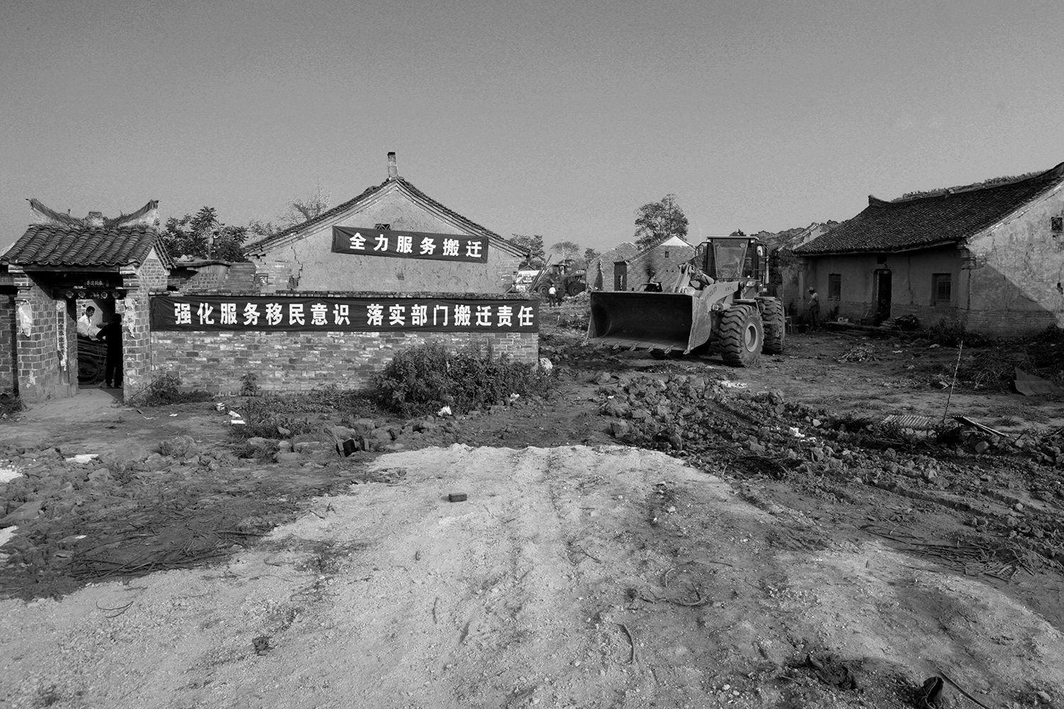 With the village largely empty of people, a bulldozer flattens a piece of ground in the village of Jinhe, August 2011.