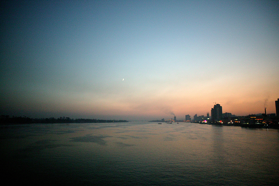Night descends over Dandong, China, seen at right along the bank of the Yalu river, October 2006.