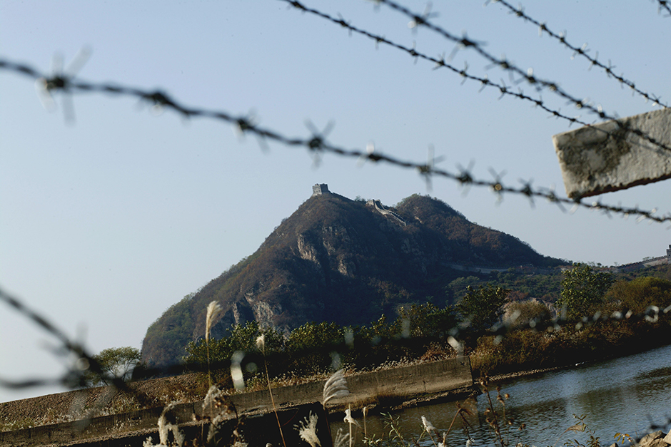A mountain in North Korea is seen through a fence constructed in 2006 that marks the North Korea-China border, October 2006. In some places, the border is a small creek where tourists and North Koreans can meet unofficially.