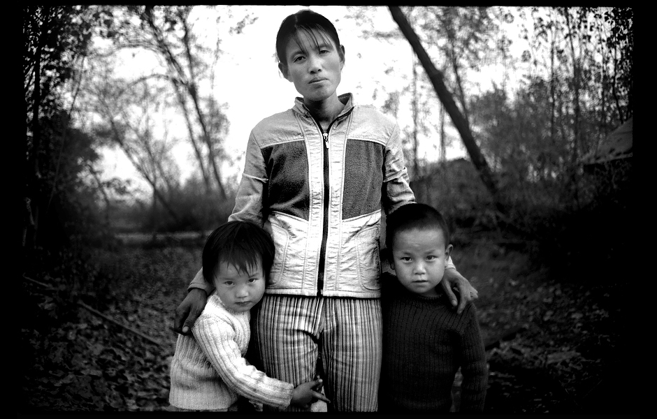 After her husband's funeral, Mrs. Wang stands with her children. At age 34, Mr. Wang died of liver cancer caused by hepatitis B—one of approximately 250,000 Chinese killed every year from hepatitis B-associated liver cancer and cirrhosis. Henan, China